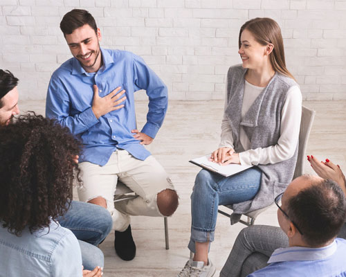People in a therapy session discussing addiction