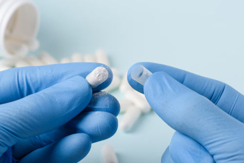Carfentanil in a capsule being opened by gloved hands
