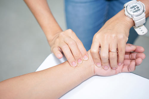 Person getting their pulse taken during drug detox