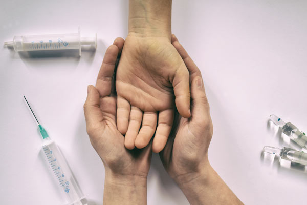 A pair of hands holding a single hand, both surrounded by syringes