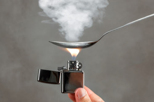 zippo lighter under a smoking spoon of heroin