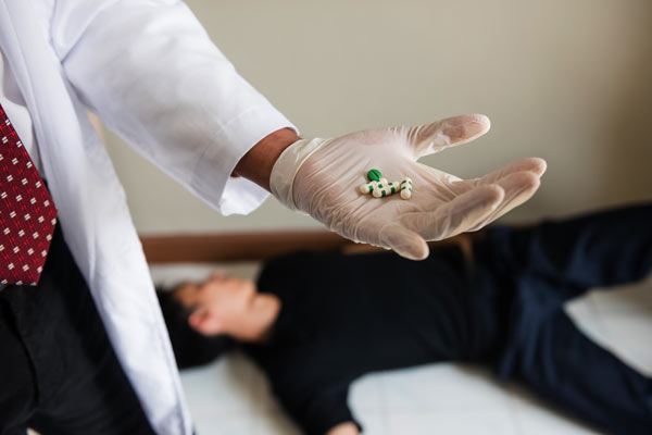 Doctor holding Brevital pills in a gloved hand