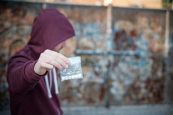 Hooded person holding suboxone pills in a plastic bag