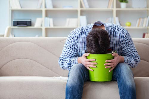 Man vomiting into a bucket, sick from Halcion withdrawal